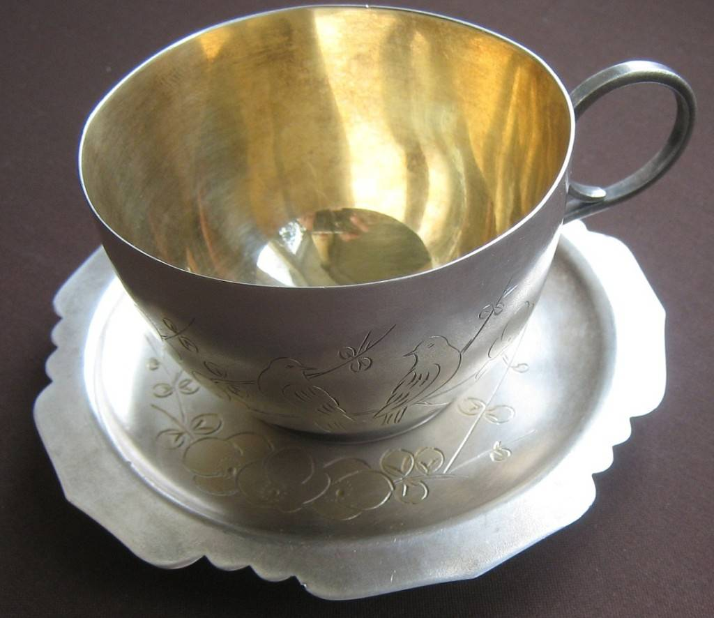 Серебряная чашка с блюдцем выглядит элегантно